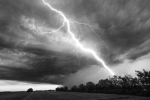 Black and white image of lightning striking a field